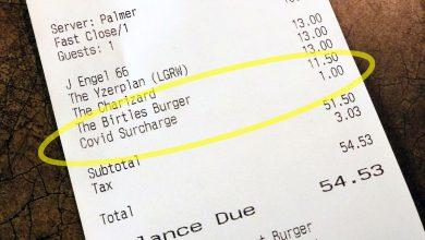 "Photo of تضيف بعض المحلات مثل المطاعم ومصففي الشعر ما يسمى بـ ""تكلفة COVID الإضافية"" إلى فواتيرها"